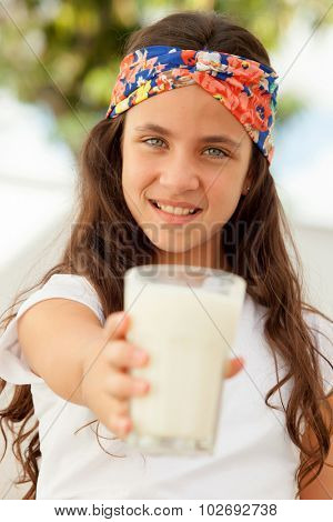 Teenager girl with blue eyes and a milk glass