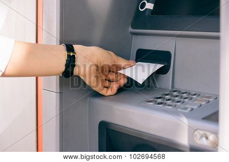 Female Hand Holding A Receipt Obtained From The Atm After Withdrawing Cash