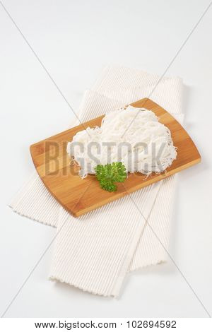 pile of cooked rice noodles on wooden cutting board and white place mat