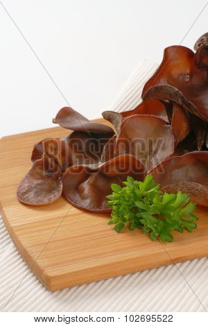 close up of cooked ear mushrooms on wooden cutting board and white place mat