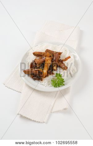 plate of roasted meat, ear mushrooms and rice noodles on white place mat