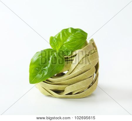tangle of green pasta decorated with leaf of basil