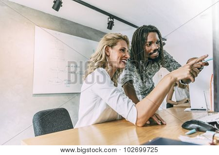 Coworkers In Office Pointing At Desktop