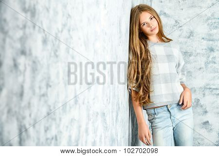 Pretty teenager girl in casual clothes posing over grunge background. Modern teen generation. Youth fashion.