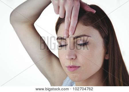 Woman meditating with hand on forehead on white background