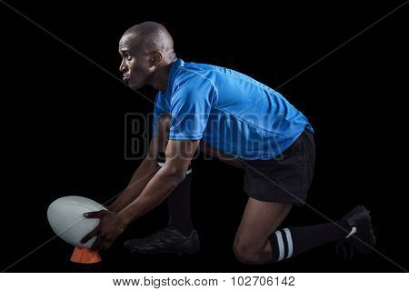 Confident rugby player looking away while keeping ball on kicking tee against black background