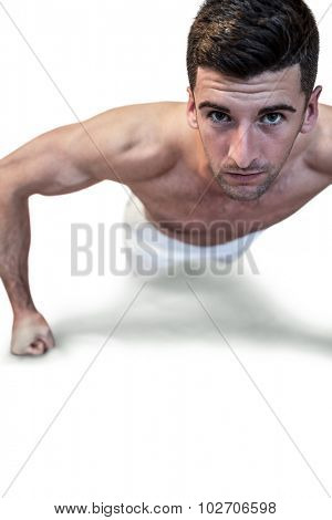 Portrait of a man doing push up with clenched fist over white background