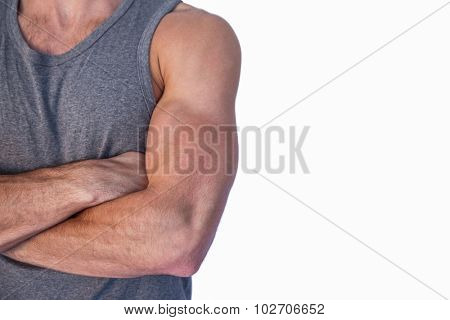 Mid section of muscular man with arms crossed against white background