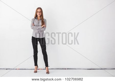 Portrait Of Beautiful Business Woman Standing Against White Wall.