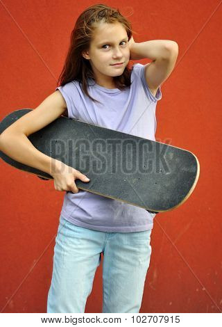 Young Teenage Girl With Skateboard In The Street