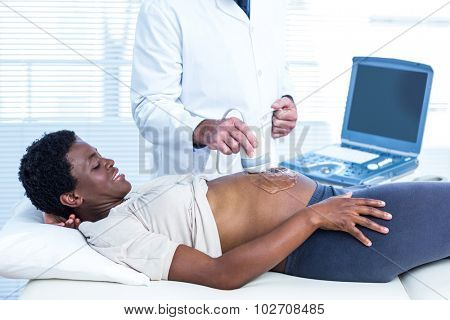 Happy pregnant woman looking at doctor while applying gel on belly