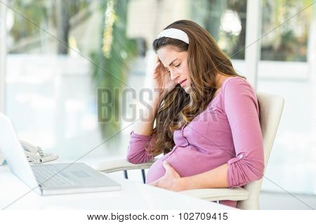Unhappy pregnant woman with headache sitting on chair at desk in home office