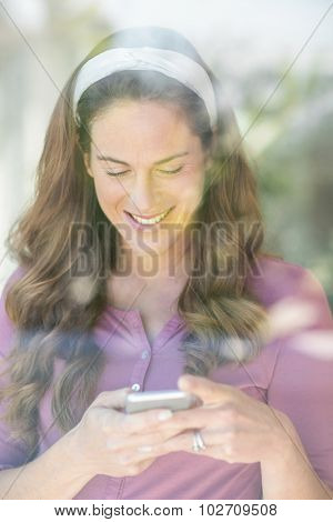 Happy woman text messaging on mobile phone by window at home