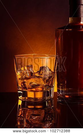 Glass Of Whiskey Near Bottle On Black Table With Reflection, Warm Tint Atmosphere