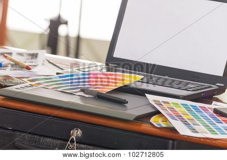 Laptop working desk with palette, colormap lying on top of it