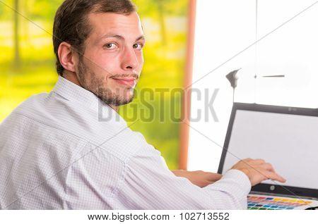 Man working on laptop turning around towards camera