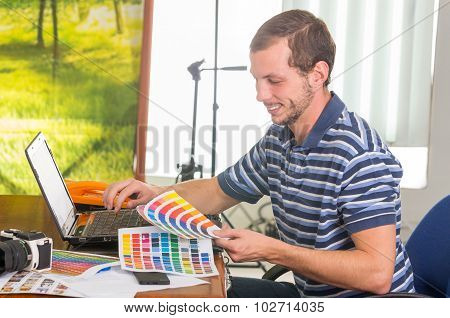 Man wearing blue white striped t-shirt sitting by work desk looking at palette, colormap