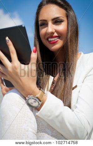 Beautiful modern businesswoman holding tablet computer