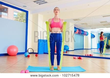 Pilates woman biceps rubber band exercise workout at gym indoor