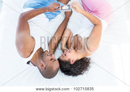 Happy husband and wife holding sonogram while relaxing on bed