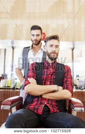 young hipster couple posing in their vintage barber shop