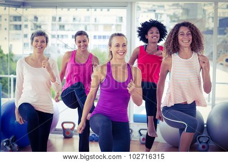 Smiling women exercising with clasped hands in fitness studio