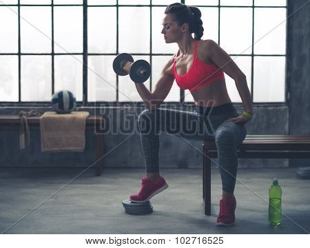 Fit Woman In Profile On Bench Lifting Weights In Loft Gym
