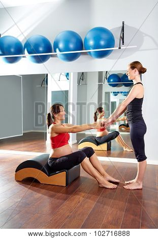pregnant woman pilates exercise with spine wave corrector and personal trainer