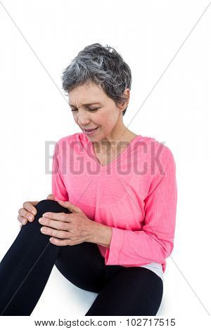 Mature woman suffering from knee pain over white bckground