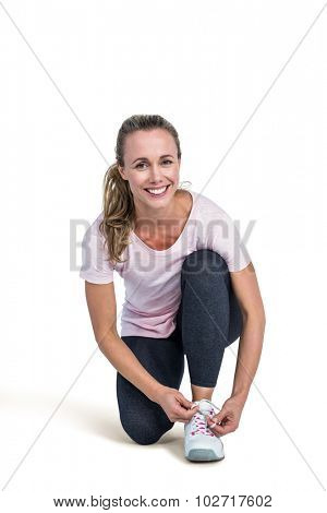 Portrait of happy sporty woman tying shoelace over white background