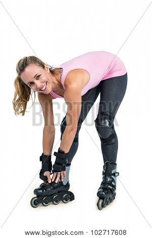 Portrait of happy sporty woman wearing inline skates over white background