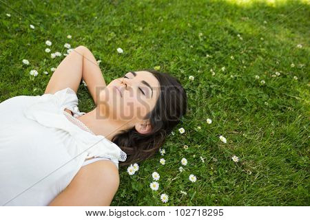 Young woman relaxing with hand behind head on grassland in park