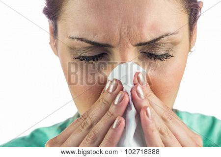 Woman suffering from cold with tissue on mouth against white background