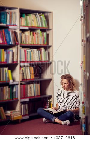 In The Library, Student Girl Or Young Woman With Book siting Between Bookstands In The Library.