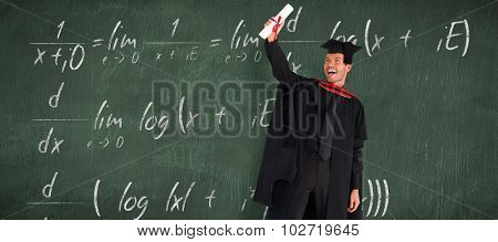 Happy attractive boy after his graduation against green chalkboard