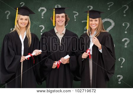 Three students in graduate robe holding a diploma against green chalkboard