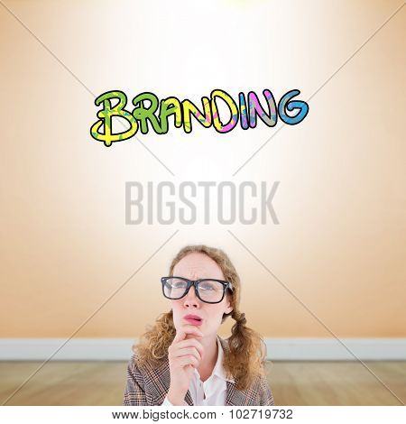 Geeky hipster woman thinking with hand on chin against room with wooden floor