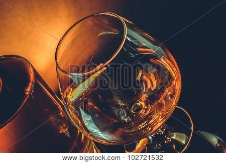 Snifter Of Brandy In Elegant Typical Cognac Glass Near Near Bottle On Black Table, Warm Tint Style