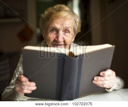 Elderly lady sits and reads big book at the table in house.