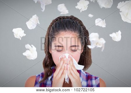 Close-up of sick woman sneezing in a tissue against grey background