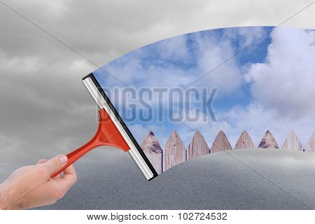 Hand using wiper against cloudy dull sky