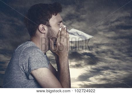Close up side view of man blowing nose against cloudy sky