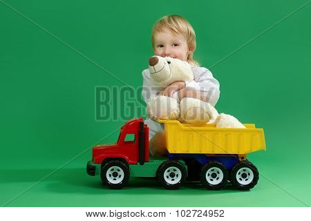 Little Boy Sitting On The Floor And Playing With Toys, Green Background