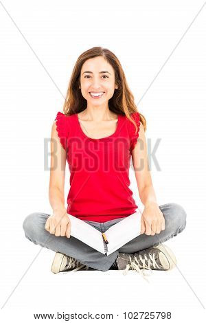 Happy Female Student Sitting On The Ground With Her Notebook
