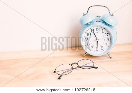 Classic Glasses And Blue Vintage Alarm Clock On Wooden Table