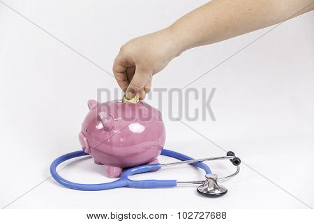 Young Girl Dropping Gold Coin in Pink Piggy Bank