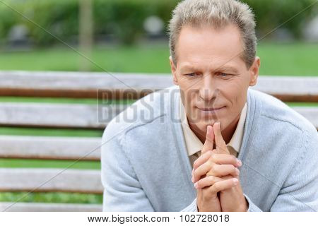 Pleasant man sitting on the bench