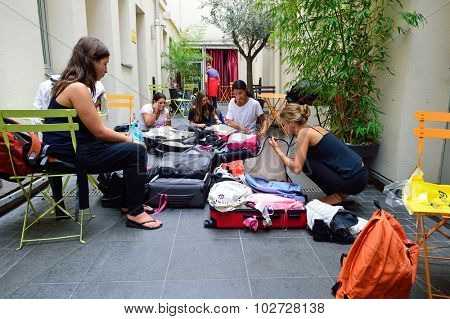 PARIS - AUGUST 08, 2015: girls collect luggage in the hostel. Hostels provide budget-oriented, sociable accommodation where guests can rent a bed in a dormitory and share a bathroom.