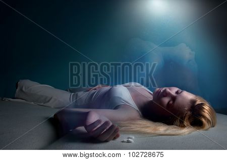 Young women lying unconscious in bed with pills