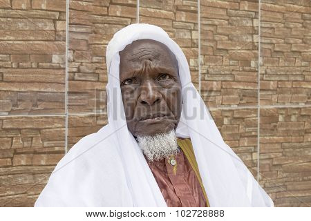 African old man sitting in front of his house, eighty years old